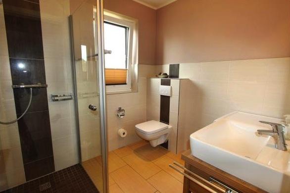 Zweites Badezimmer mit Waschmaschine und verglaster Raindance-Dusche
